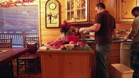 ohař : men cut up slabs of elk meat on a kitchen counter