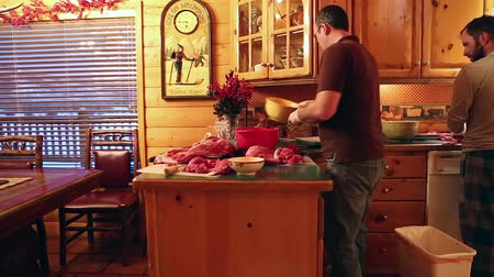descamação : a man butchers elk meat on his kitchen counter  from his hunt. Stock Footage