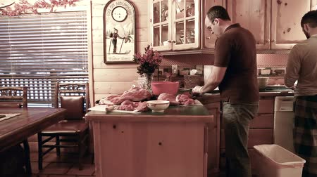 hentes : a man butchers elk meat on his kitchen counter  from his hunt. Stock mozgókép