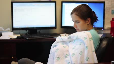 szoptatás : A young working mother breastfeeds her baby at the office
