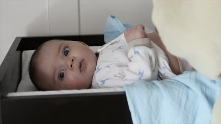 царапина : A mother changes her newborn baby boys diaper on a changing table in his bedroom Стоковые видеозаписи