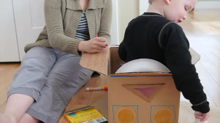 kalmak : A stay at home mother makes a spaceship from a card board box and colors it with her toddler boy