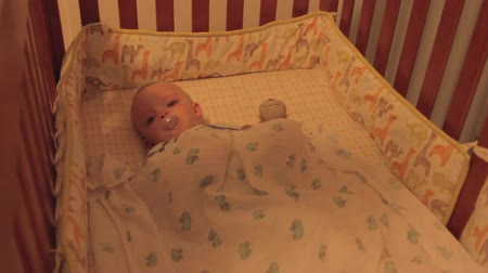 cobertor : Mother putting her baby boy to bed in his crib