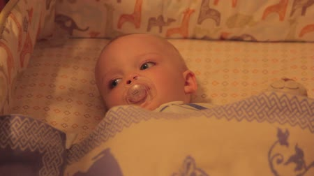 mroczne : a mother puts her toddler boy to bed in his crib