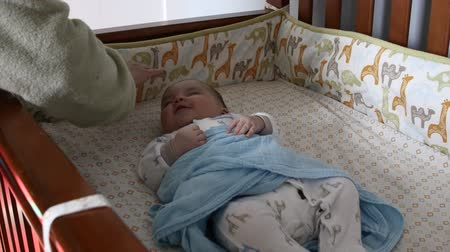 мать : A tired young mother puts her newborn baby boy into his crib for a nap in his bedroom