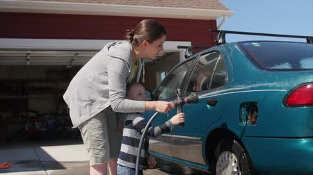 cera : A toddler boy helps his mother wash the car with a rag and soapy water in the driveway of his house