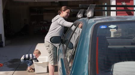 autó : A toddler boy helps his mother wash the car with a rag and soapy water in the driveway of his house