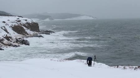 cape breton : photographer at stormy ocean shore