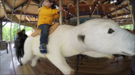 koń : A little toddler at the hogle zoo in Utah riding a fun carousel with animals Wideo
