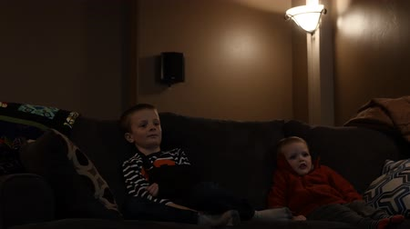 filmes : Children watch a movie inside a home theater room while sitting on the couch