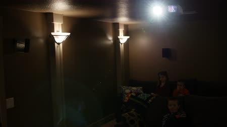 sofá : Children watch a movie inside a home theater room while sitting on the couch