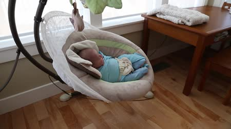 cobertor : a newborn baby boy sleeping in a swing in the house