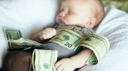 yirmi : A baby lying in a pile of cash. Babies are expensive