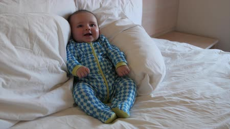 кровать : A newborn baby boy lying in a hotel bed while his family packs their suitcases and gets ready to leave for home
