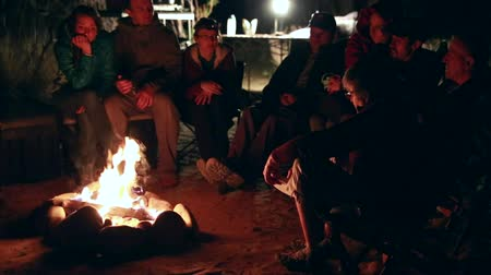 şenlik ateşi : family sits around a campfire at night while camping in the desert