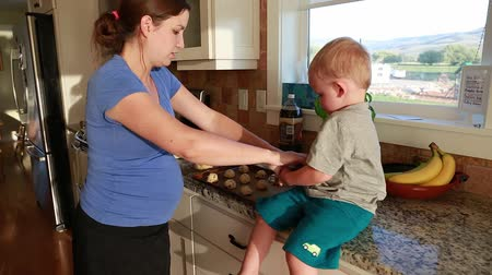 мать : a little boy toddler makes chocolate chip cookies with his pregnant mother in their kitchen