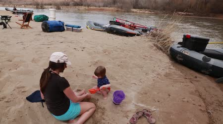 row : families running the san juan river in southern utah on river rafts through the desert Stock Footage
