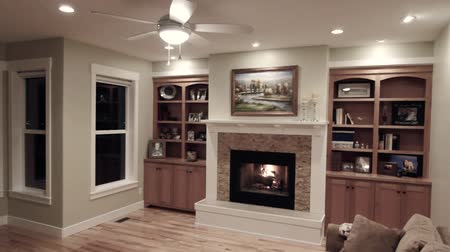 kabine : a jib shot of a cozy fireplace and mantle in a beautiful sitting room Stok Video
