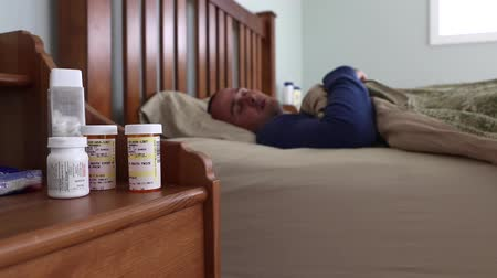 guy home : a sick man sleeping in bed next to his prescription pill bottles