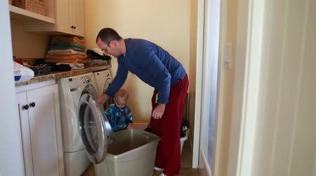 myjnia : a toddler helps his dad put clothes in the washing machine