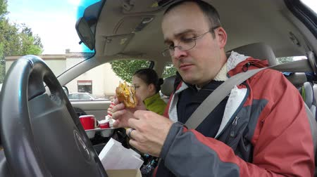 нездоровое питание : A young family eating fast food hamburgers and fries in the car from the drive through while traveling