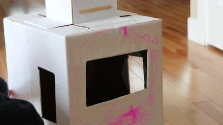 caseiro : An adorable toddler boy coloring and playing with a robot suit made from cardboard boxes