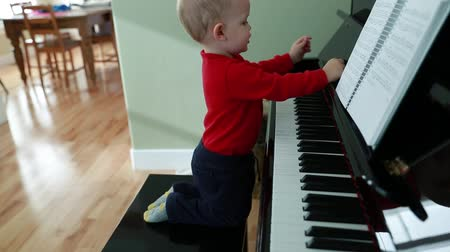 пианино : a little toddler playing on a black upright piano in his home