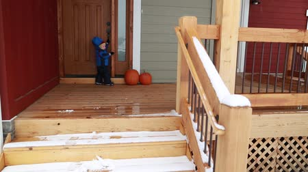 womanhood : toddler playing on home patio outside in snow Stock Footage