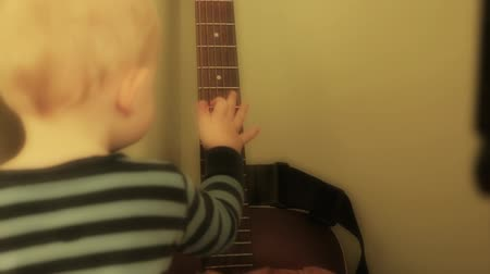 пианино : a little baby boy strumming a guitar and playing with a drum
