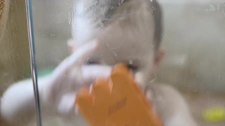 küvet : A toddler plays in the shower with his mom Stok Video