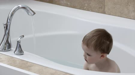 küvet : A cute little boy getting clean in a large bath tub in the bathroom
