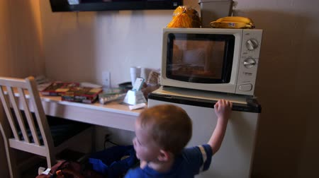 akşam yemeği : A family cooks pizzas for dinner in a hotel microwave