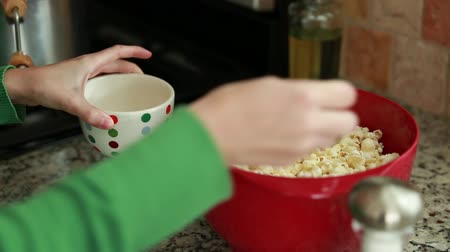 попкорн : woman adds salt and butter to popcorn