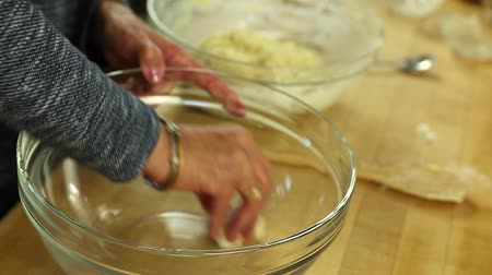 piekarz : woman buttering bowl to make orange rolls