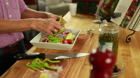 řek : woman cuts a green pepper for a greek salad