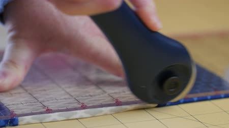 têxtil : Woman cuts fabric with a rotary cutter Vídeos