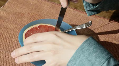 rind : Woman cutting a grapefruit for breakfast