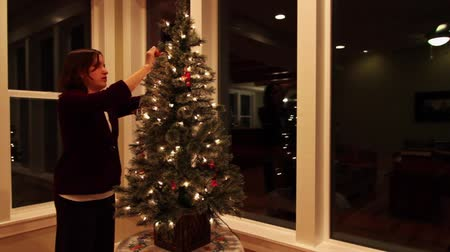 światło : a woman decorates a small christmas tree in a house