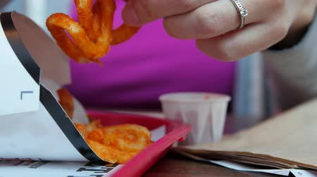 fry : Woman eating curly fries at a fast food restaurant