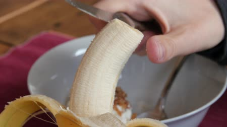 tápláló : Woman eats a banana with breakfast Stock mozgókép