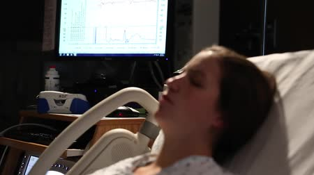 emek : woman in labor having contractions at the hospital with nurses in the room Stok Video