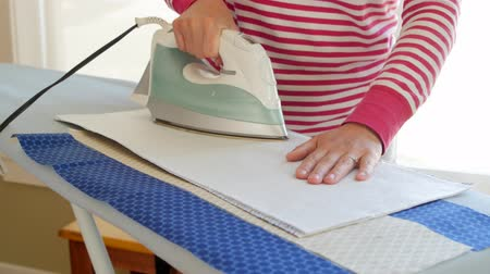 trabalhos domésticos : Woman ironing her sewing projects