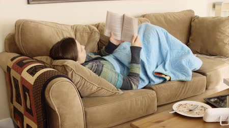 sofá : A young woman lies comfortably on a couch and reads a good book in her house
