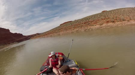 row : families running the san juan river in southern utah on river rafts through the desert timelapse Stock Footage