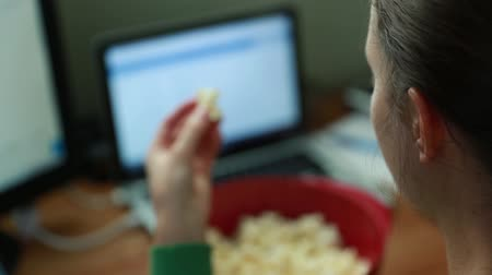 healthy office : a woman working in her home office and snacking on popcorn Stock Footage