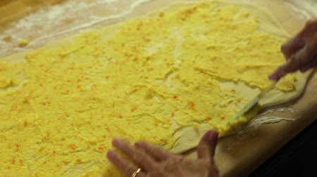 descamação : woman spreads topping on orange roll dough Stock Footage
