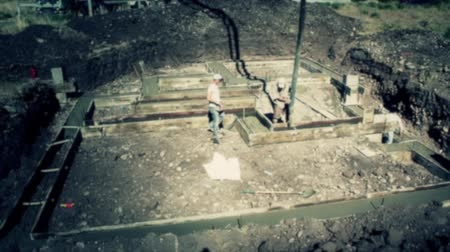 myjnia : Construction workers prepare and pour the footings of a house.