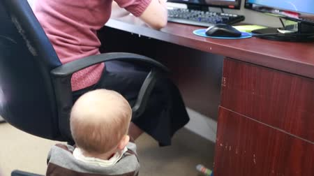 bezrobotny : a working mother in the office on her computer with her toddler Wideo