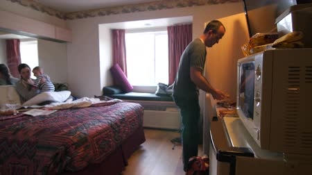 mikrohullámú : A young family cooks frozen pizzas for dinner in a hotel room microwave