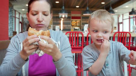 картофель фри : A family eating a lunch at a clean and modern fast food restaurant